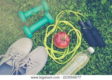 Gray sports shoes sneakers, dumbbells, bottle of water, red apple and yellow skipping rope on fresh green grass.