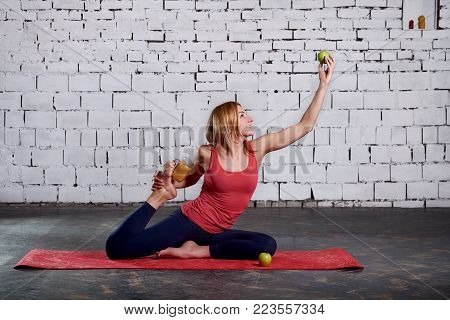 Yoga Vegetarianism. Yoga girl is holding smoothies and apple. Woman doing yoga and health lifestyle with fresh fruits. Side view portrait of beautiful young woman wearing pink tank top working out against a white brick wall, doing yoga or pilates exercise