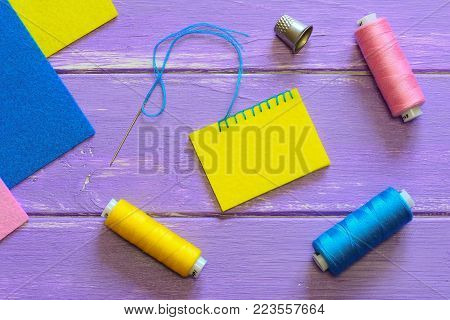 Easy blanket stitch photo. How to sew a blanket stitch. Wool or synthetic felt sewing projects for kids. Colourful felt sheets, thread set, thimble on a wooden background. Top view
