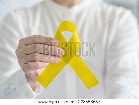 Yellow ribbon symbolic color for suicide prevention and Sarcoma Bone cancer awareness in person's hand