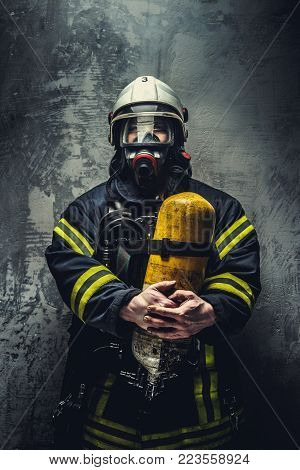 Firefighter in oxygen mask holds yellow oxygen tank.