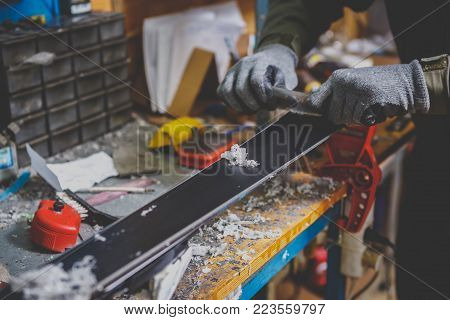 A male worker in a ski service workshop repairs the sliding surface of the skis. Close-up of a hand with a plastic scrapper for removing wax, removing new wax. Theme repair of ski curb. poster