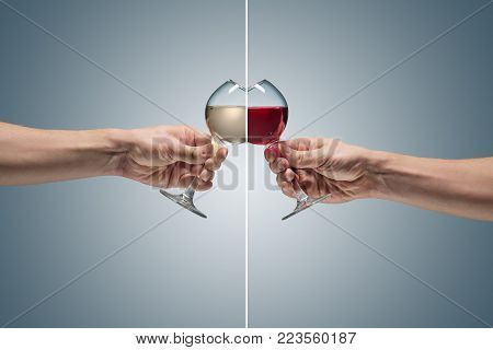 Close-up view of two glasses with red and white wine in male hand. concept of confrontation, differences in taste and preference