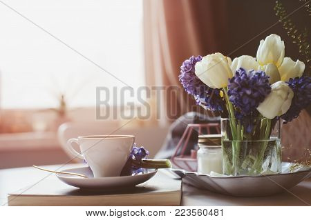spring morning at home with cup of coffee, book and flowers on white table. Seasonal decoration, cozy living, hygge concept
