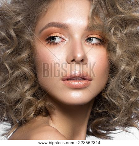 Beautiful blonde girl with curls and gentle make-up. Beauty face. Photos shot in the studio.