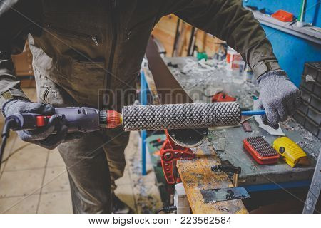 A man in work clothes a repairman in a workshop ski service a ski slip surface, Base polishing, final ski polishing. In the hands of an electric brush rotor brush. Theme repair of ski curb poster