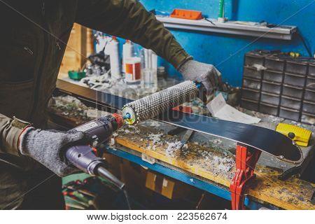 A man in work clothes a repairman in a workshop ski service a ski slip surface, Base polishing, final ski polishing. In the hands of an electric brush rotor brush. Theme repair of ski curb