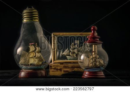 Ships in bottles inside glass cases of various shapes: a still life of vintage decoration items.