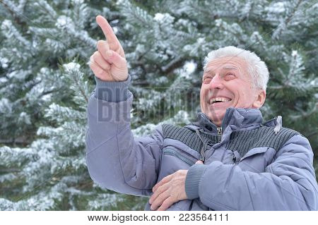 senior happy man in warm clothes posing outdoors in winter