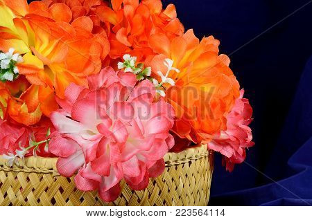 Bouquet in a basket of Artificial flower rose peony red white yellow and orange bright color made of synthetic fabric and plastic. Flowers lie on the table on dark blue fabric. Objects close up.