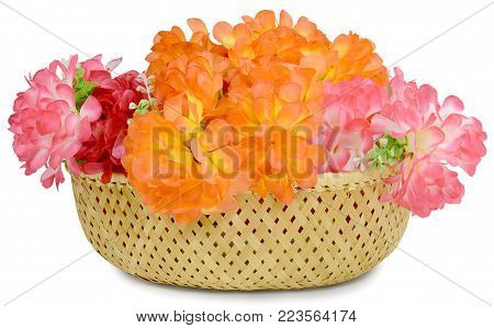 In basket beautiful large bouquet of Artificial flowers rose peony red white yellow and orange bright color made of synthetic fabric and plastic. Items pictured close up isolated on white background.