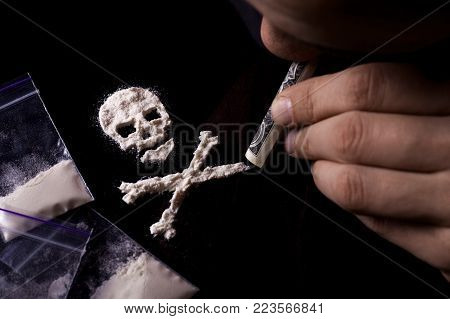 Drug dependence Kills. Junkie man sniffing a line of cocaine in the shape of a skull through a dollar, sachets with a dose. Black background. Narcotics concept.