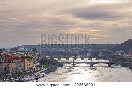 Panorama of the old part of Prague from the Letna park. Beautiful view on the bridges over the river Vltava at cloudy winter day. View on charles bridge at sunset. Czech Republic.