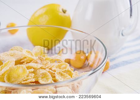 Bowl with corn flakes, jug of milk and empty bowl for prepared delicious breakfast.The concept of healthy breakfast, corn flakes with milk and fruit on wooden table, close up.