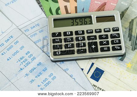 Financial tax or debt calculation for office salary man  concept as calculator on pile of euro banknotes with numbers on carbon salary slips.