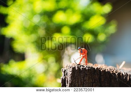Miniature people, man working on timber on green nature background, using as construction and industrial concept