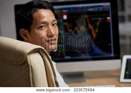 Portrait of Asian financial analyst at his workplace