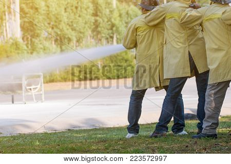 Firemen using extinguisher and water from hose for fire fighting at firefight training of insurance group. Firefighter wearing a fire suit for safety under the danger training case.