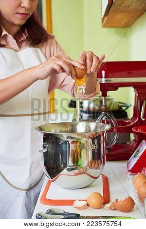 Female baker cracking eggs into mixer bowl to make pie dough