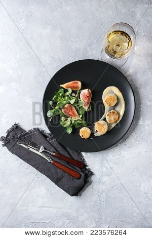 Fried scallops with lemon, figs, sauce and green salad served on black plate with glass of white wine and cutlery over gray texture background. Top view, space. Plating, fine dining