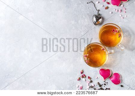 Love Valentines day greeting card with two glasses of hot tea, rose buds, heart shape homemade cookies as gift, pink sugar, tea strainer over gray texture background. Top view, space