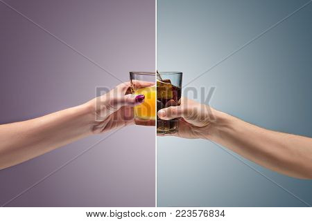 The woman holding orange juice glass and Drink cola in glass at studio. concept of confrontation, differences in taste and preference