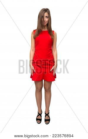 Embarrassed, shy and humble girl in red dress in stockings and in high heels shoes is standing with her legs wide apart isolated on white background.