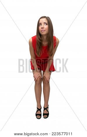 Pensive laughing girl in red dress in stockings and in high heels shoes is bending her knees and looking up isolated on white background.