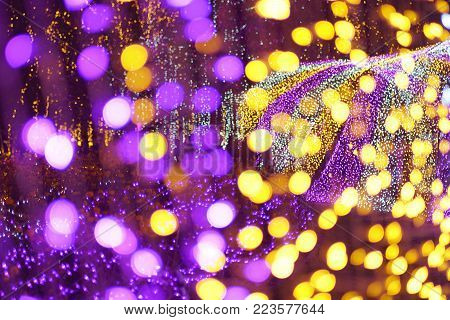 Illuminated violet and golden bokeh circular light diffused background.