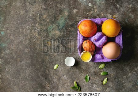 Easter greeting card with colored yellow orange eggs in purple box with quail eggs, yolk and green leaves over old metal background. Top view, copy space