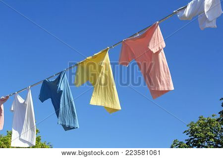 T-shirts Hanging On A Clothesline In Front Of Blue Sky
