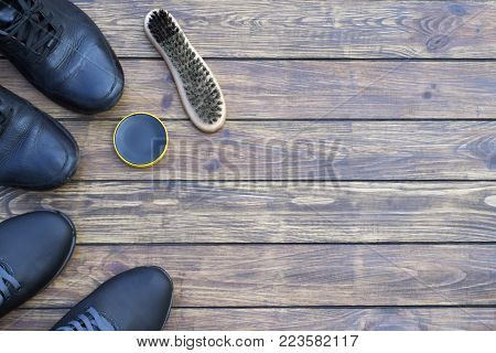 new and old men's black shoes on laces. shoe polish and a new shoe brush. on a wooden background. view from above. place for inscription