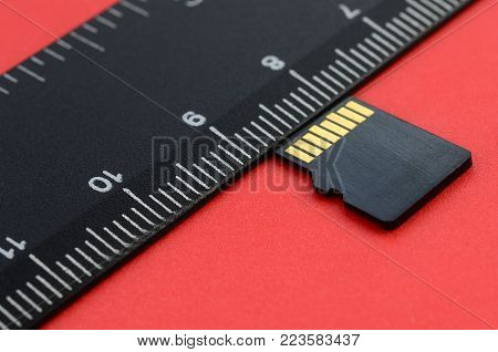 Small micro SD memory card lie on a red background next to a black ruler. A small and compact data and information store