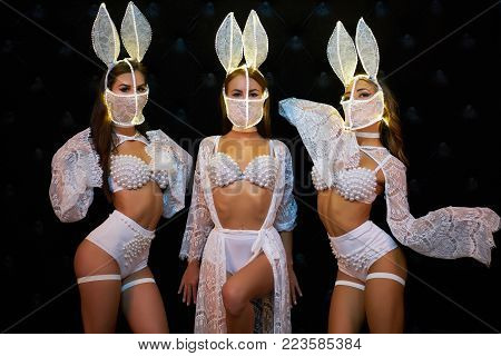 Group of Sexy girsl in white lingerie and LED masks. Go-go dancers. Three Strippers posing in the studio on a black background. Girls show ballet in the night club. show-program in a night club