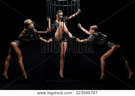 Beautiful sexy go-go performers isolated on black. Sexy girl dance group posing in black underwear near the cage. Three strippers.