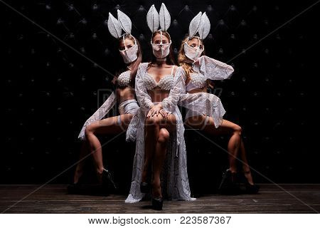 Beautiful sexy go-go performers isolated on black. Sexy girl dance group posing in white underwear. Three strippers.