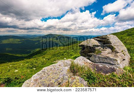 boulders on the grassy slope. rolling hills of Carpathian mountains in the distance. beautiful summer landscape under the blue sky with some clouds