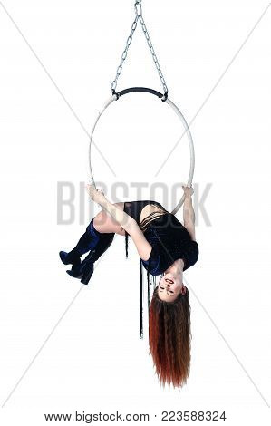 Aerial acrobat in a hoop. Young woman performs the acrobatic elements in the air ring. Studio shooting, isolated on white background.