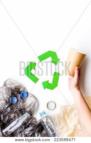 Recycle plastic and polyethylene waste. Botlles and bags near green recycle sign on white background top view.