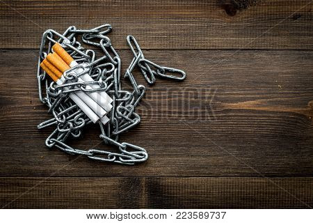 Quit smoking. Cigarettes in chains on dark wooden background top view.