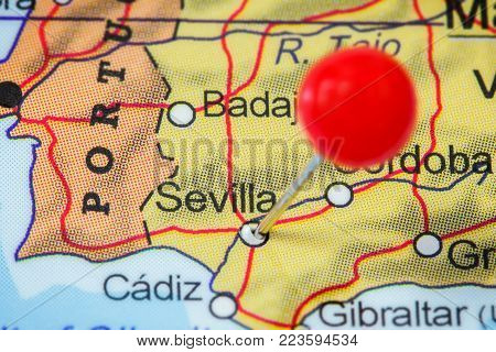 Close-up of a red pushpin in a map of Sevilla, Spain.