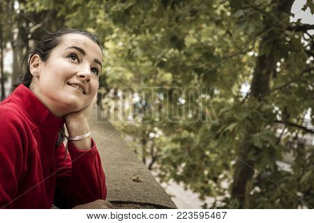 Side view of cheerful dreamy woman leaning on handrail and looking at trees