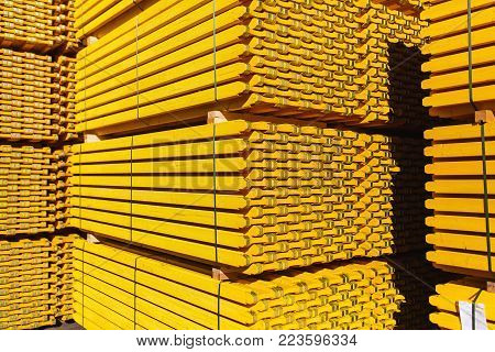New yellow wooden formwork stacked in a warehouse in large piles. Materials for the construction and erection of concrete structures.