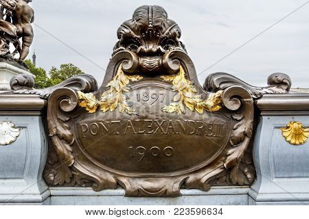 Beautiful historic metallic plate decorated with golden paint in Pont Alexandre III in Paris