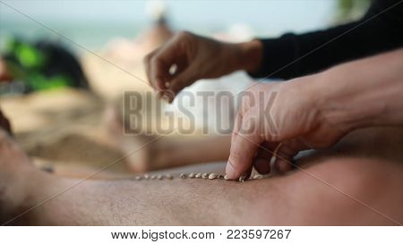 Lazy time. Feet of the man on the beach in the sand on a summer day. Each puts a grain of sand on the foot of the other gays on vacation.