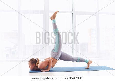 Beautiful young woman practices yoga asanaEka Pada Ashtanga Namaskara at the bright yoga class with large windows