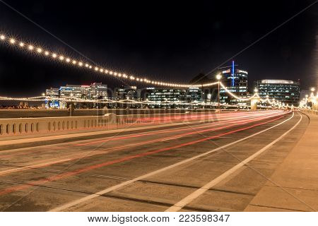 TEMPE, AZ - OCTOBER 25, 2017: The city skyline of Tempe, Arizona at night from the Mill Avenue Bridge across the Salt River at Tempe Town Lake