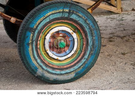 multi-colored trailer wheel, tractor, on the background of sand, road rusty bolts, rubber tire tire spring shock absorber metal car disk