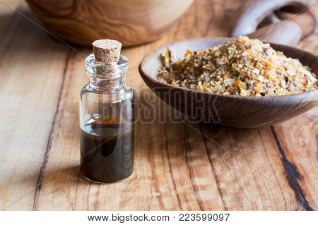 A bottle of myrrh essential oil with myrrh resin in the background