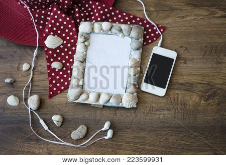 The frame for a photo memoir, or inscriptions, is made with seashells. on a wooden table with a phone, headphones and a hat